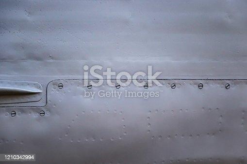 487808089 istock photo Aircraft skin close up. Rivets on gray metal. 1210342994