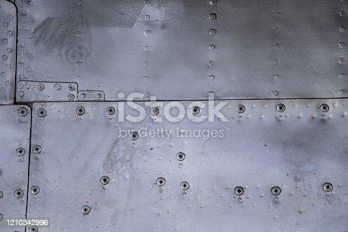 487808089 istock photo Aircraft skin close up. Rivets on gray metal. 1210342996