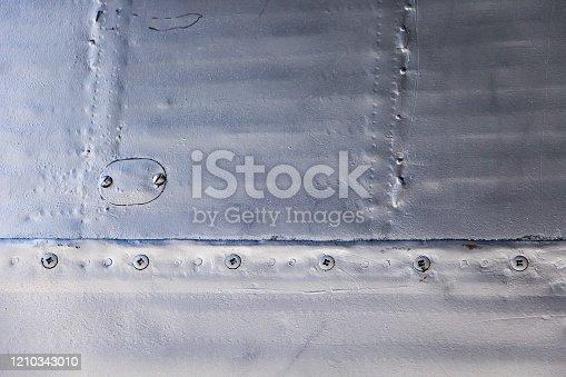 487808089 istock photo Aircraft skin close up. Rivets on gray metal. 1210343010