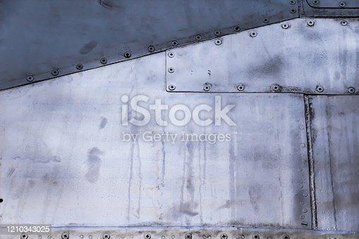 487808089 istock photo Aircraft skin close up. Rivets on gray metal. 1210343025