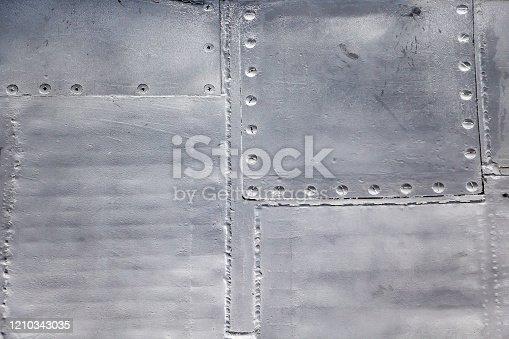 487808089 istock photo Aircraft skin close up. Rivets on gray metal. 1210343035