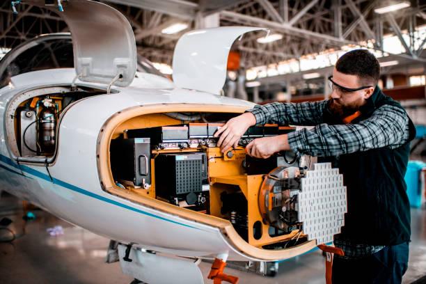 Flugzeugtechniker, der Service auf einer Radaranlage eines Flugzeugs in einem Wartungshangar leistet – Foto