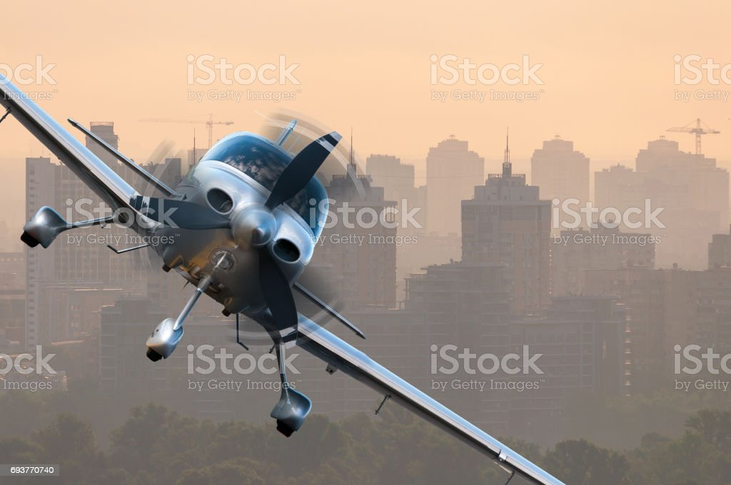 Aircraft traveling over city buildings and high-rise skyscrapers. Concept of privat airline travel business and civil aircrafts stock photo