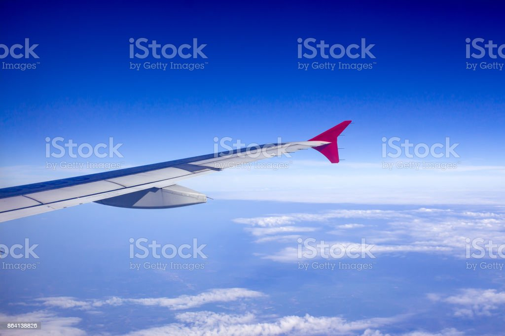 Aircraft wing against blue sky from its windows. royalty-free stock photo