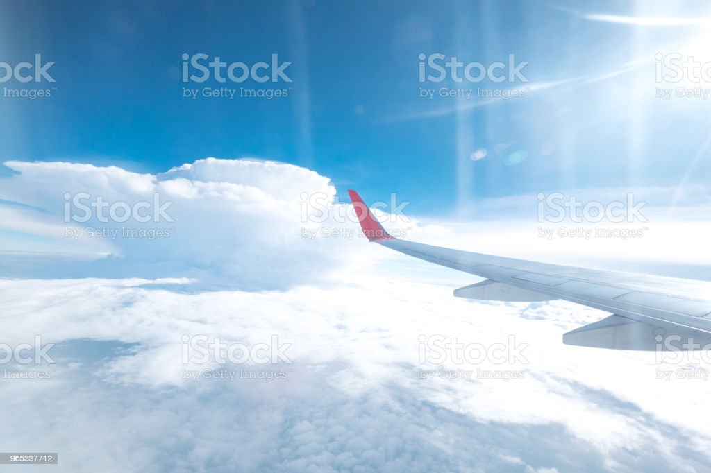 Aircraft wing flying above the beautiful clouds with sunlight in the morning. Traveling concept. stock photo
