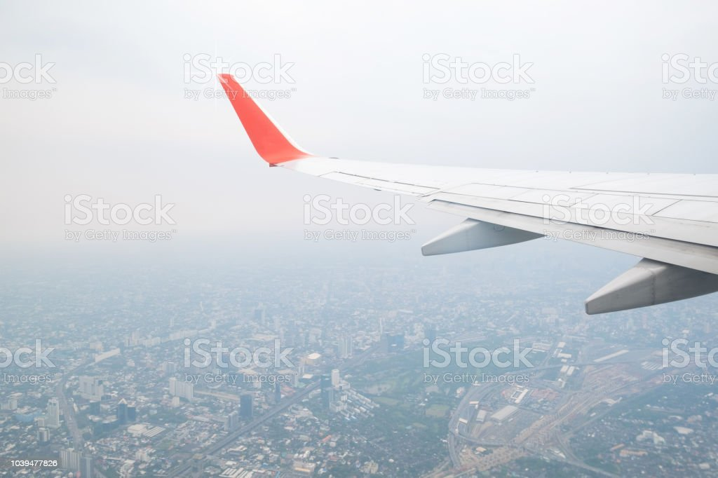 Aircraft wing flying view from window of city in the morning....