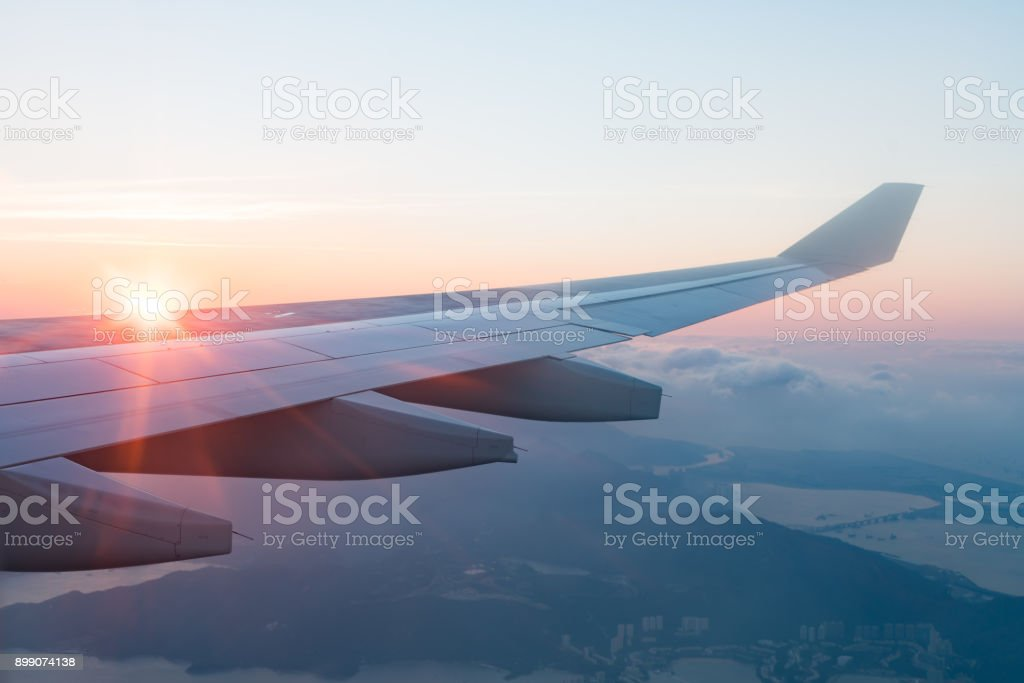 Wing of an airplane with Morning sunrise. Photo applied to tourism...