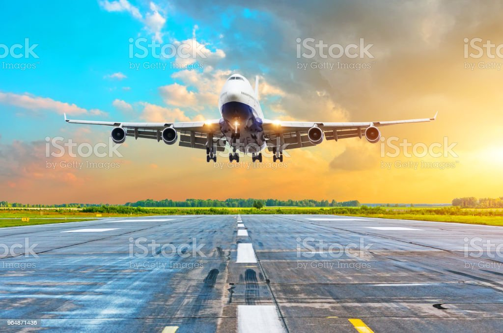 Aircraft with four engines flying arrival landing on a runway in the evening during a bright red gradient sunset. royalty-free stock photo