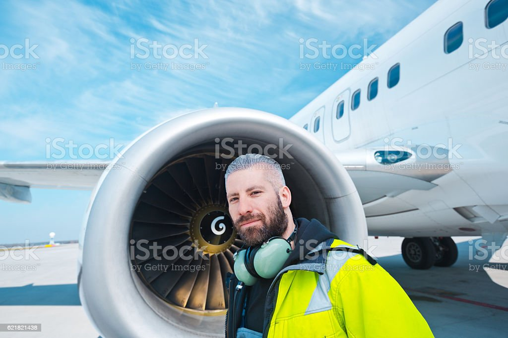 Aircraft worker in front of airplane Aircraft engineer standing outdoor in front of airplane, looking at camera. Adult Stock Photo