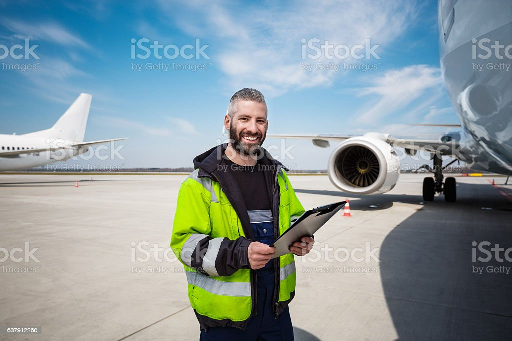 Aircraft worker in front of airplane with checklist Aircraft engineer holding clipboard in hands standing outdoor in front of airplane, smiling at camera. Adult Stock Photo