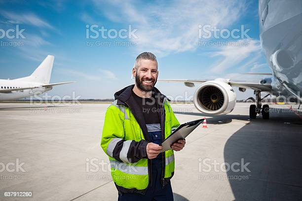 Aircraft Worker In Front Of Airplane With Checklist Stock Photo - Download Image Now