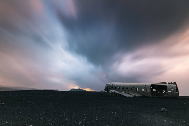 Aircraft wreckage on black sands beach in Iceland The crashed United States Navy plane at Solheimasandur Beach on the south coast of Iceland. sólheimasandur stock pictures, royalty-free photos & images