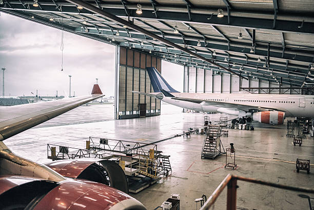 Aircrafts in hangar Two wide body aircrafts are parked and servicing in hangar. airplane hangar stock pictures, royalty-free photos & images
