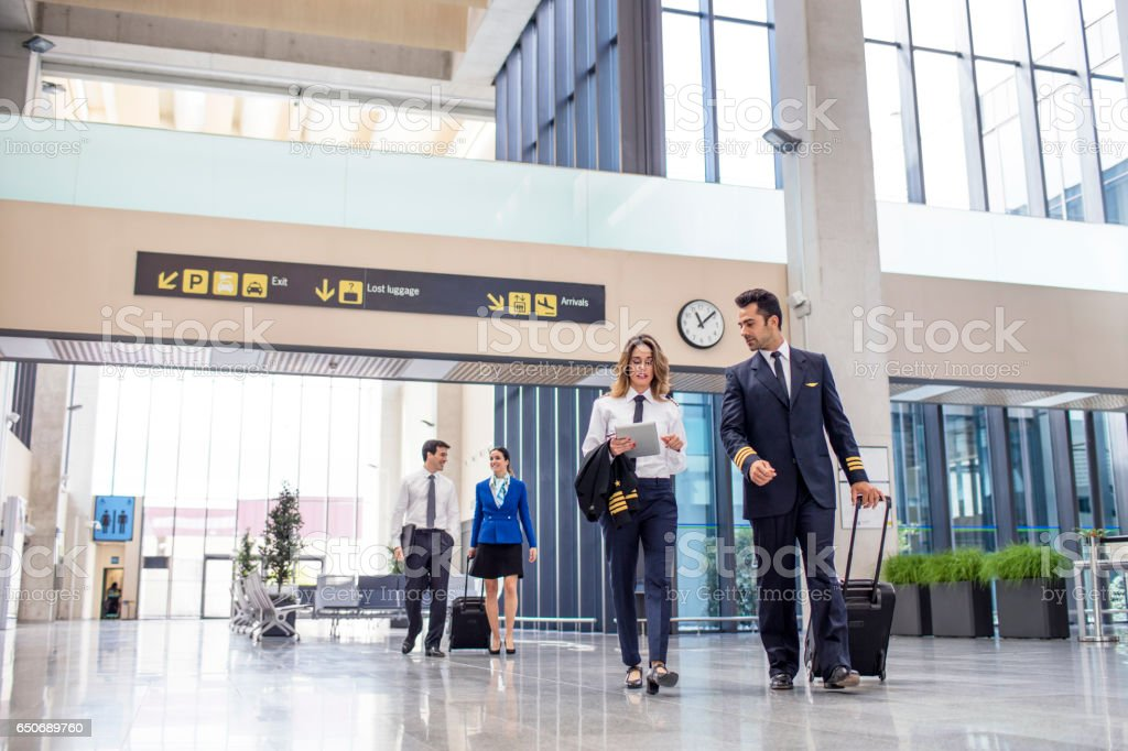 Aircrew with luggage and tablet walking in airport stock photo