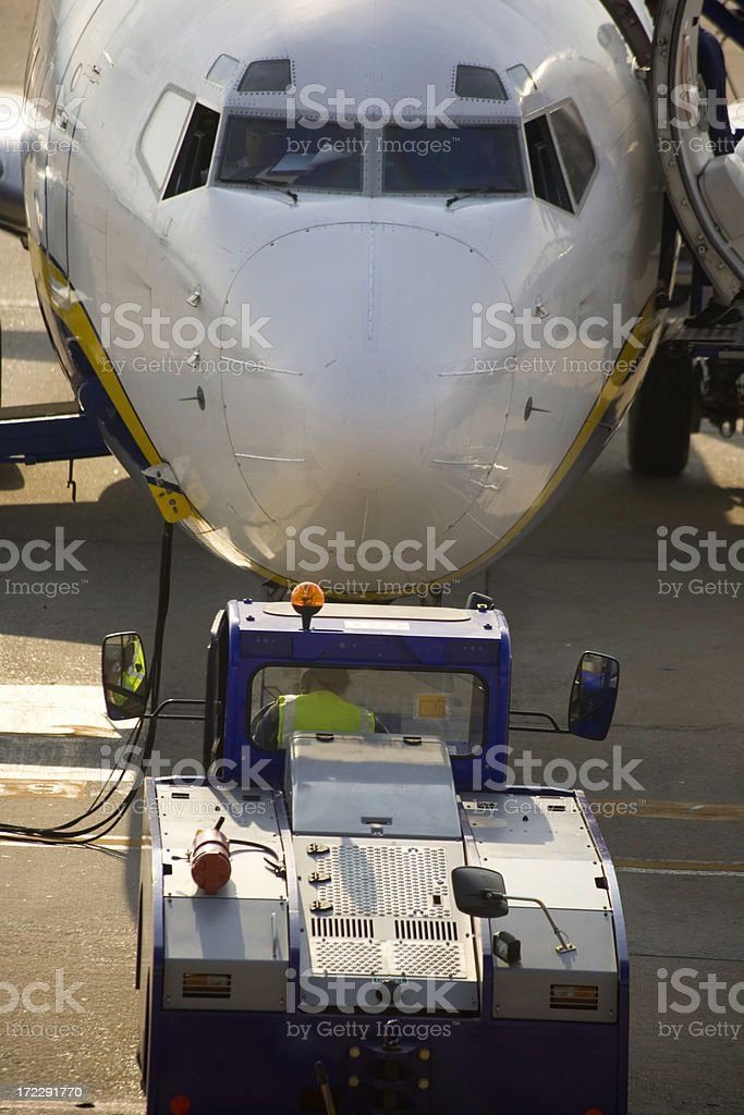 Airctraft tractor moving a plane royalty-free stock photo