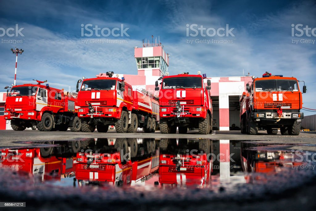 Airfield fire trucks with reflection in a puddle near garage boxes стоковое фото