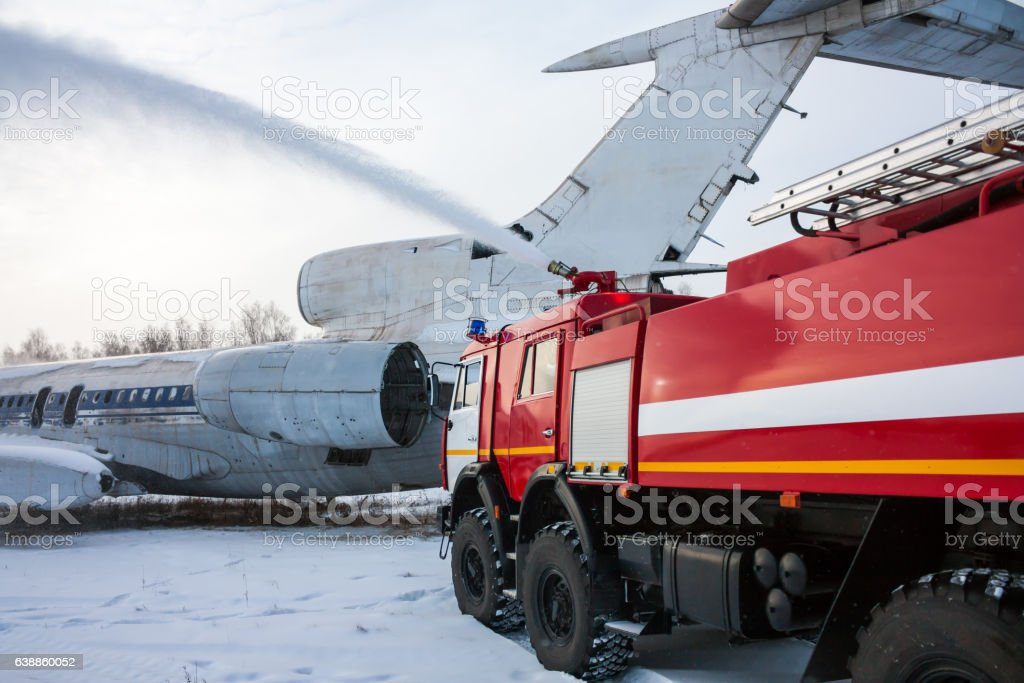 Airfield firetruck extinguishes aircraft after emergency landing стоковое фото