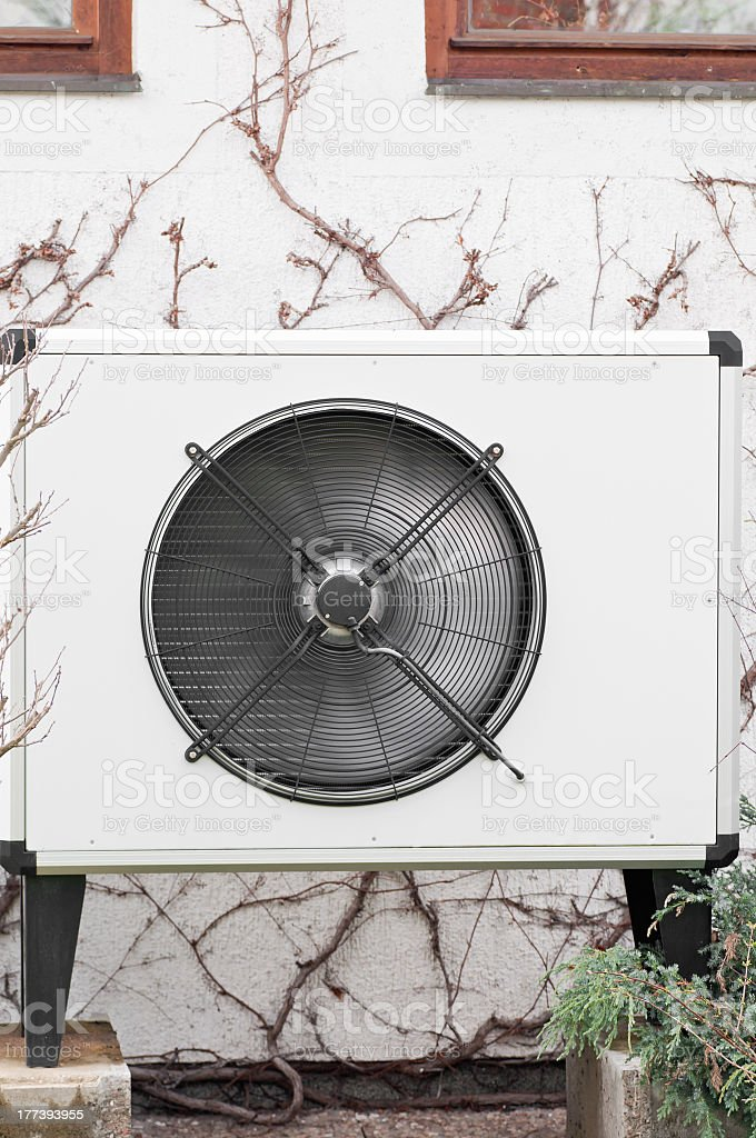 Air/Heat fan mounted on outside wall with vines growing royalty-free stock photo