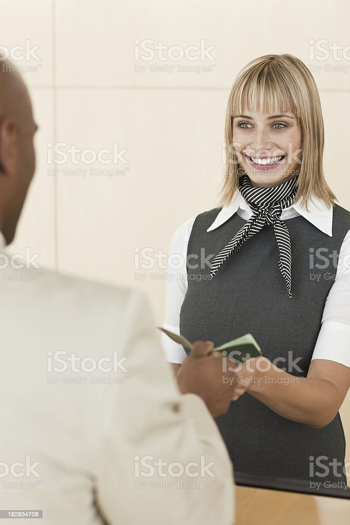 Airline Attendant Hands Documentation Back to a Businessman stock photo