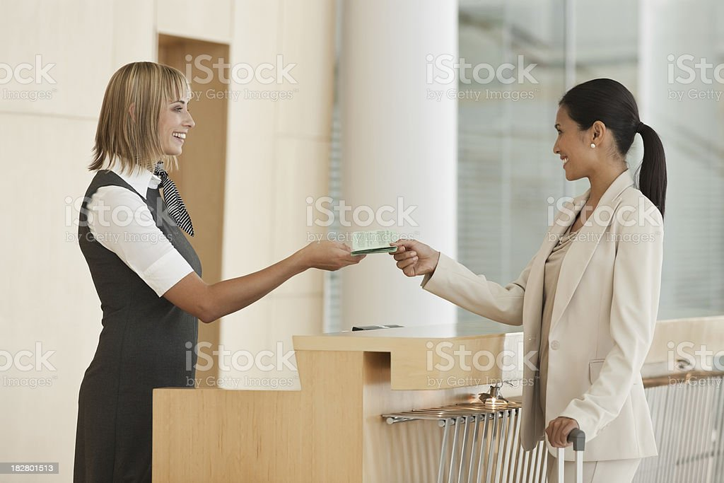 Airline Attendant Hands Documentation Back to a Businesswoman stock photo