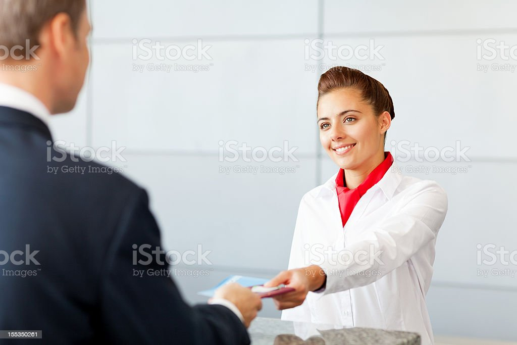 Airline Check In Attendant Handing Tickets To Passenger royalty-free stock photo