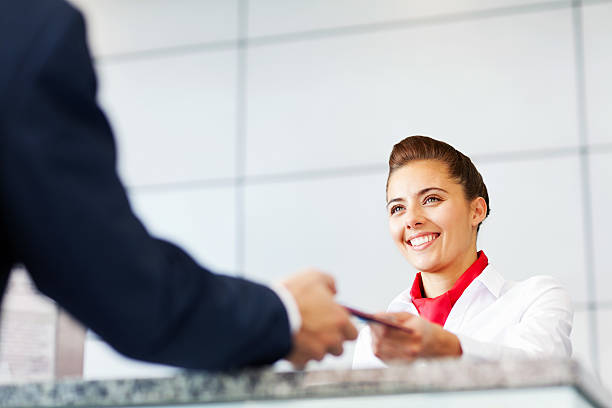 Airline Check In Attendant Handing Tickets To Passenger Low angle view of female cabin crew giving ticket to the passenger. Horizontal Shot. cabin crew stock pictures, royalty-free photos & images