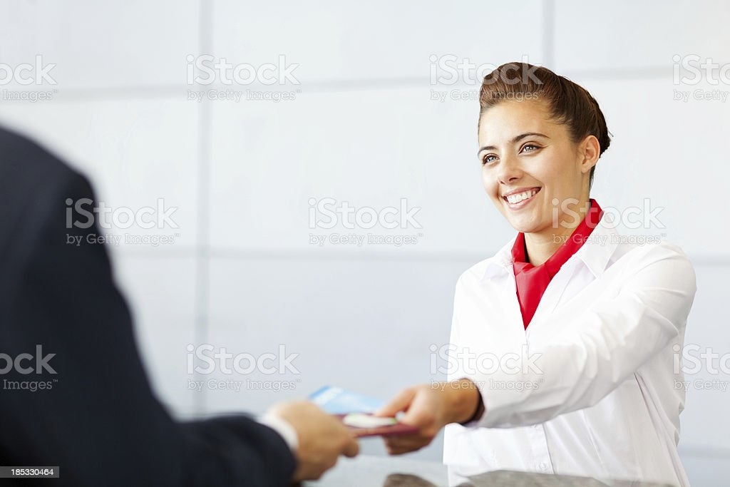 Airline Check In Attendant Handing Tickets To Passenger stock photo