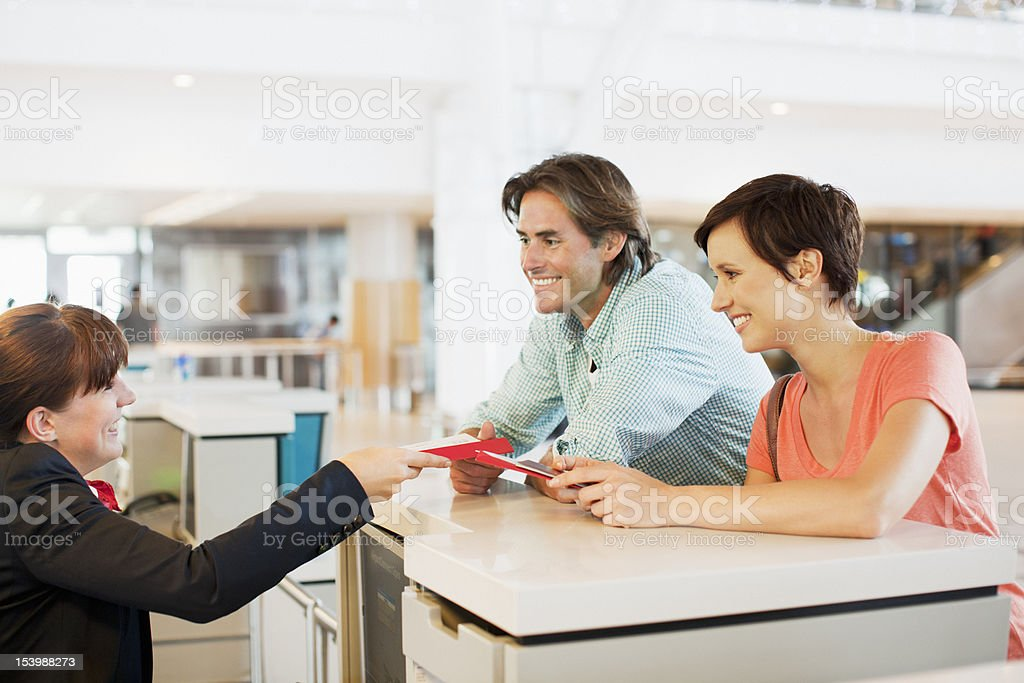 Airline check-in attendant assisting couple at counter in airport stock photo