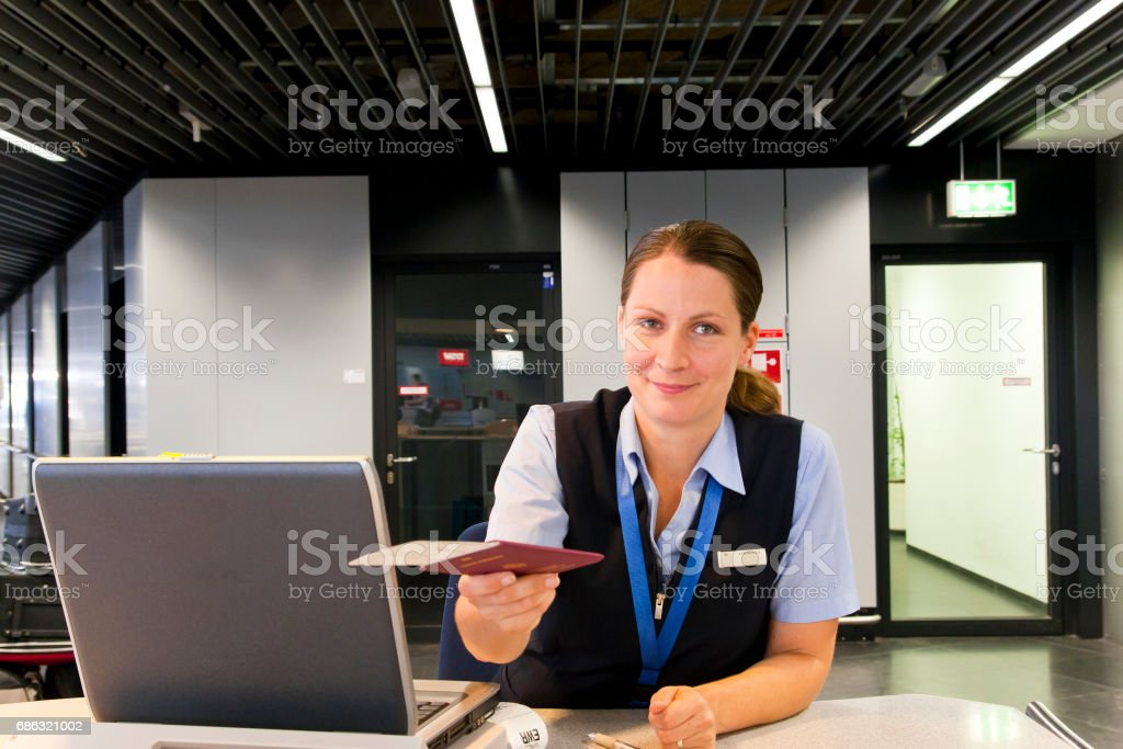 Airline Employee handing Ticket and Passport to Customer stock photo