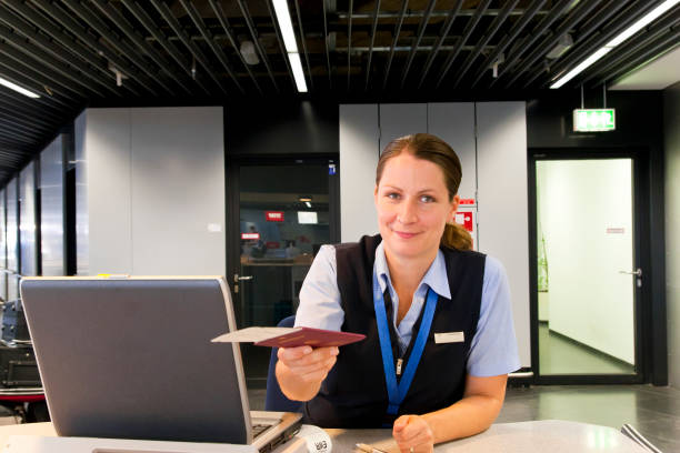 Airline Employee handing Ticket and Passport to Customer Airline Employee handing Ticket and Passport to Customer customs official stock pictures, royalty-free photos & images