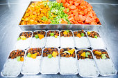 Cooked airline food in an aluminium foil placed in a row.