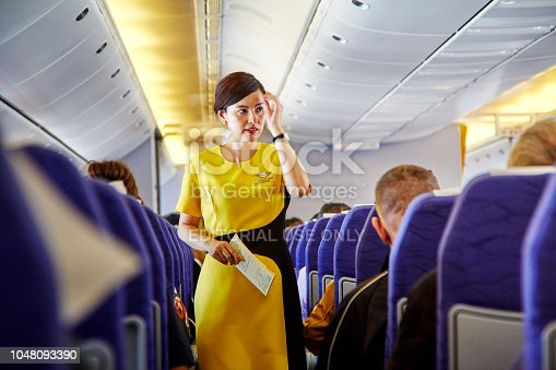 823006998 istock photo Airline nokscoot Interior of airplane with passengers on seats and stewardess in Yellow uniform at the aisle. 1048093390