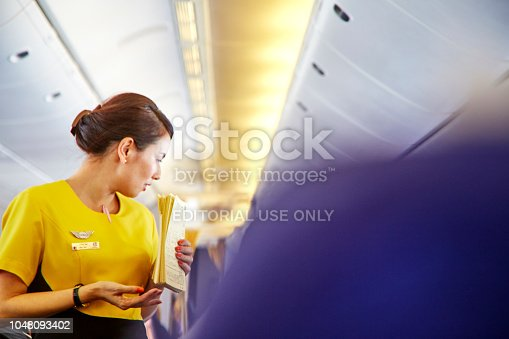 823006998istockphoto Airline nokscoot Interior of airplane with passengers on seats and stewardess in Yellow uniform at the aisle. 1048093402