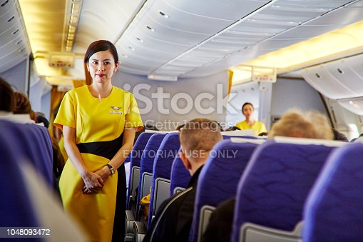 823006998 istock photo Airline nokscoot Interior of airplane with passengers on seats and stewardess in Yellow uniform at the aisle. 1048093472