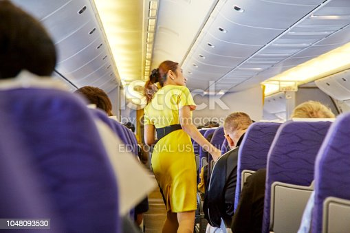 823006998istockphoto Airline nokscoot Interior of airplane with passengers on seats and stewardess in Yellow uniform at the aisle. 1048093530