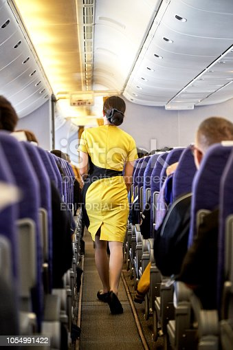 823006998 istock photo Airline nokscoot Interior of airplane with passengers on seats and stewardess in Yellow uniform at the aisle. 1054991422