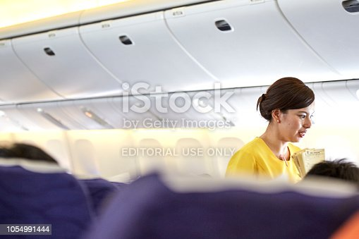 823006998 istock photo Airline nokscoot Interior of airplane with passengers on seats and stewardess in Yellow uniform at the aisle. 1054991444