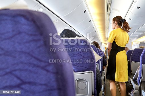 823006998 istock photo Airline nokscoot Interior of airplane with passengers on seats and stewardess in Yellow uniform at the aisle. 1054991446