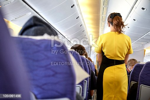823006998 istock photo Airline nokscoot Interior of airplane with passengers on seats and stewardess in Yellow uniform at the aisle. 1054991456