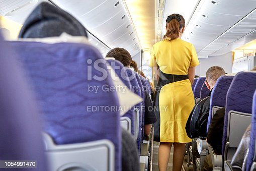 823006998 istock photo Airline nokscoot Interior of airplane with passengers on seats and stewardess in Yellow uniform at the aisle. 1054991470