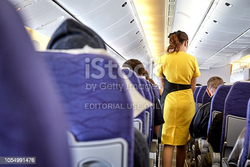 823006998 istock photo Airline nokscoot Interior of airplane with passengers on seats and stewardess in Yellow uniform at the aisle. 1054991476