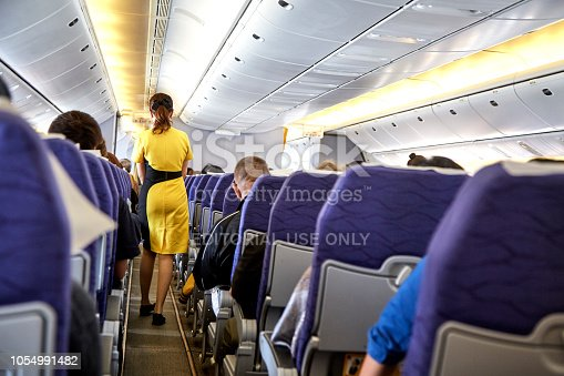 823006998 istock photo Airline nokscoot Interior of airplane with passengers on seats and stewardess in Yellow uniform at the aisle. 1054991482