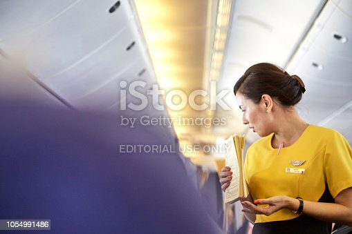 823006998 istock photo Airline nokscoot Interior of airplane with passengers on seats and stewardess in Yellow uniform at the aisle. 1054991486