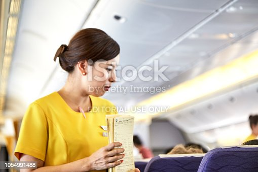 823006998 istock photo Airline nokscoot Interior of airplane with passengers on seats and stewardess in Yellow uniform at the aisle. 1054991488