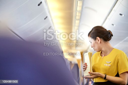 823006998 istock photo Airline nokscoot Interior of airplane with passengers on seats and stewardess in Yellow uniform at the aisle. 1054991500