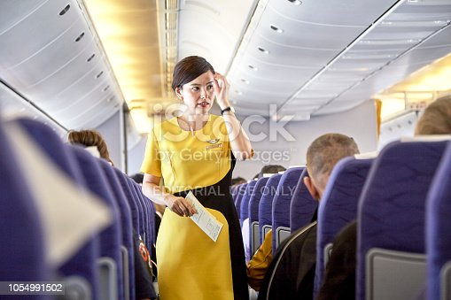 823006998 istock photo Airline nokscoot Interior of airplane with passengers on seats and stewardess in Yellow uniform at the aisle. 1054991502