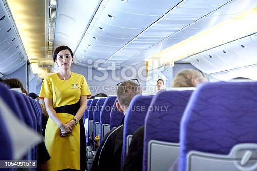 823006998 istock photo Airline nokscoot Interior of airplane with passengers on seats and stewardess in Yellow uniform at the aisle. 1054991518