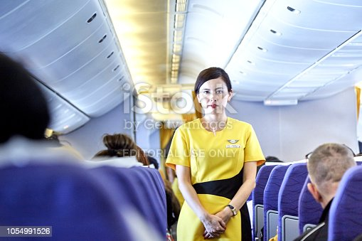 823006998 istock photo Airline nokscoot Interior of airplane with passengers on seats and stewardess in Yellow uniform at the aisle. 1054991526