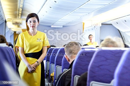 823006998 istock photo Airline nokscoot Interior of airplane with passengers on seats and stewardess in Yellow uniform at the aisle. 1054991532