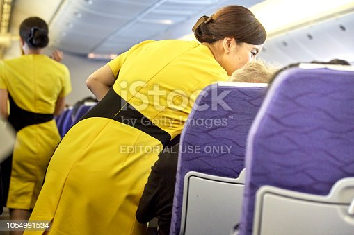 823006998 istock photo Airline nokscoot Interior of airplane with passengers on seats and stewardess in Yellow uniform at the aisle. 1054991534